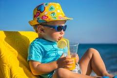 El niño bebe el jugo contra el mar Fotos de archivo libres de regalías