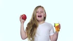 El niño bebe el jugo de un vidrio y sostiene una manzana Fondo blanco Cámara lenta metrajes