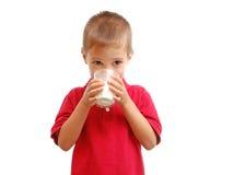 El niño bebe la leche Foto de archivo