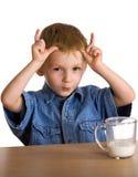 El niño bebe los claxones de las demostraciones de la leche Fotos de archivo libres de regalías