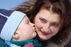 El niño besa a su madre Fotos de archivo