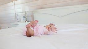 El niño bonito en vestido rosado miente encendido detrás en una cama en casa almacen de metraje de vídeo