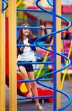 El niño bonito, muchacha sube en el montante en el patio Imagenes de archivo