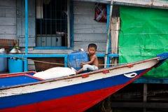 El niño camboyano se sienta en el frente del barco Imágenes de archivo libres de regalías