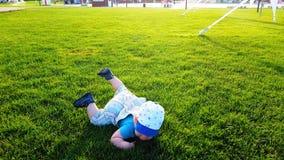 El niño camina torpe el un césped verde claro y caídas almacen de video