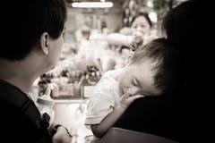El niño cansado siente cansado y duerme en el hombro de su madre imagenes de archivo