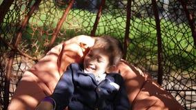 El niño caucásico lindo feliz, muchacho divertido alegre, alegre del niño del bebé está montando en el oscilación en día de fiest almacen de video