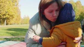 El niño caucásico llora y va a la mamá Consuelos y abrazos de la madre él metrajes