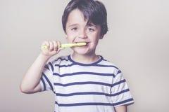 El niño cepilla sus dientes Imagenes de archivo