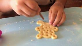 El niño cocina para arriba las galletas, las manos del niño hace las galletas almacen de metraje de vídeo