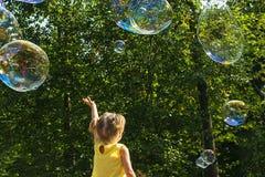 El niño coge burbujas de jabón imagenes de archivo