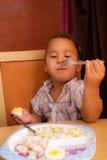 El niño come Imagenes de archivo