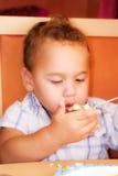 El niño come Imagen de archivo libre de regalías