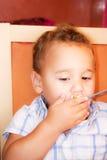 El niño come Imagen de archivo
