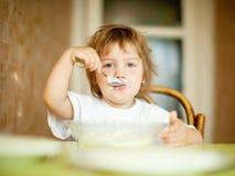 El niño come de la placa con la cuchara Imágenes de archivo libres de regalías