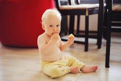 El niño come debajo de la tabla Imagen de archivo libre de regalías