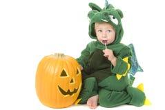 El niño come el lollipop mientras que desgasta el traje del dragón Imagenes de archivo