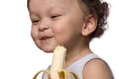 El niño come el plátano. Fotos de archivo