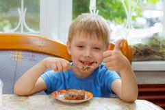 El niño come la cuchara de postre de la torta Foto de archivo libre de regalías