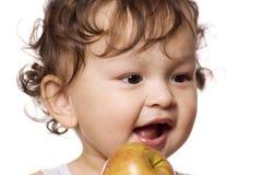 El niño come la manzana. Imagen de archivo