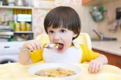 El niño come la sopa con la cocina de las bolas de carne en casa Foto de archivo libre de regalías