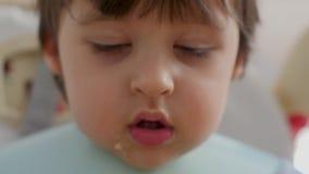 El niño come la sopa con una cuchara del hierro metrajes