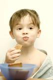 El niño come las galletas Imágenes de archivo libres de regalías
