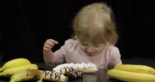 El niño come el plátano, la fresa con el chocolate derretido y la crema azotada metrajes