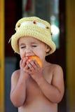 El niño come un melocotón sabroso Imagenes de archivo