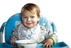 El niño come Un niño en la tabla en el jardín y el hogar Delia concentró Bebé hermoso, hermoso Imagenes de archivo