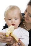El niño come un plátano. Fotografía de archivo