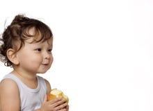 El niño come una manzana. Imagen de archivo