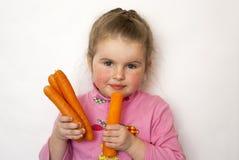 El niño come zanahorias Foto de archivo