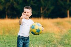 El niño con el balón de fútbol muestra MUY BIEN, en el jardín de la casa con el fondo de la hierba, sonriendo Deporte del niño y  Fotos de archivo