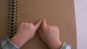 El niño con deficiencias visuales leyó el libro de braille con la fuente de caracteres almacen de video