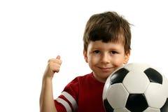 El niño con el balón de fútbol muestra OK Imágenes de archivo libres de regalías