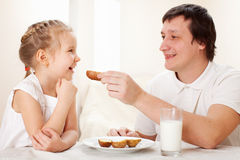 El niño con el padre desayuna Fotos de archivo