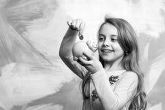 El niño con la cara feliz ahorra el dinero para el futuro foto de archivo