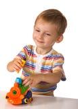 El niño con la máquina del juguete Foto de archivo libre de regalías