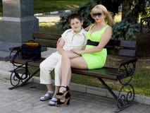 El niño con la madre se sienta en un banco en el parque Fotos de archivo