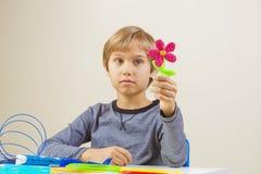 El niño con la pluma de la impresión 3d creó una flor foto de archivo