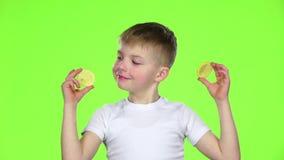 El niño con las rebanadas de limón las lame y muestra muecas Pantalla verde Cámara lenta almacen de metraje de vídeo