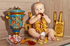 El niño con un samovar y un sushka Imagenes de archivo