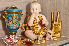 El niño con un samovar y una cuchara de madera Imágenes de archivo libres de regalías