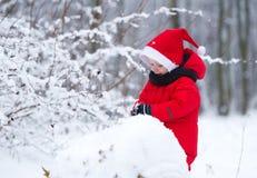 El niño construye un muñeco de nieve de la nieve Imágenes de archivo libres de regalías