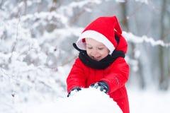 El niño construye un muñeco de nieve de la nieve Fotos de archivo