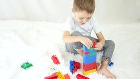 El niño construye una torre de bloques coloreados en un fondo blanco El concepto de desarrollo infantil almacen de video