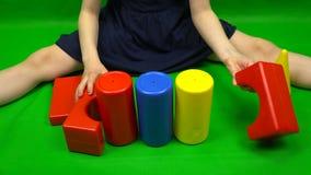 El niño construye una torre de cubos del azul, del amarillo y del rojo almacen de metraje de vídeo
