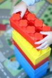 El niño construye una torre fuera de constructor de los ladrillos Foto de archivo libre de regalías