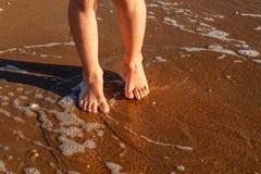 El niño corre en la resaca en la playa en el agua imágenes de archivo libres de regalías